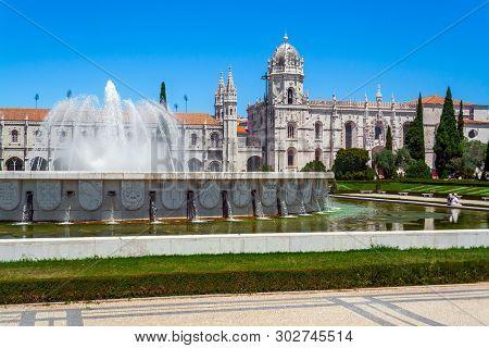 Lisbon, Portugal. Jeronimos Monastery or Abbey aka Santa Maria de Belem seen from Jardim da Praca do Imperio Garden and Square. Fountain with water jets spray