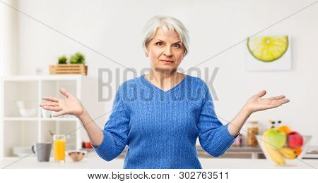 gesture, emotion and old people concept - portrait of senior woman in blue sweater having no idea and shrugging over kitchen background
