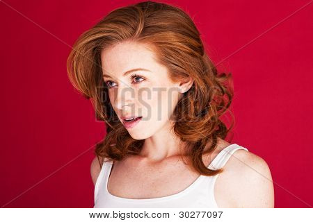 Pretty redhead woman looking to to the left of the frame with her mouth slightly open in disbelief.