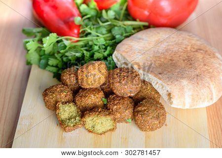 Falafel Balls, Sweet Red Pepper , Pita-arabian Bread And Green Fresh Parsley  On Wood Rustic Backgro