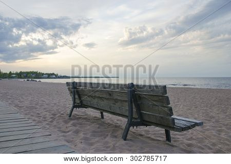 Rear View Of An Unoccupied Wooden Bench On A Deserted Sandy Beach By The Lake In The Evening Against