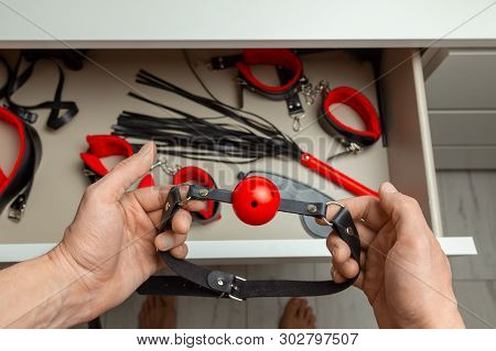 Set of erotic toys for BDSM. The game of sexual slavery with handcuffs, whip, gag and leather straps. In the closet of the dresser. Intimate games poster
