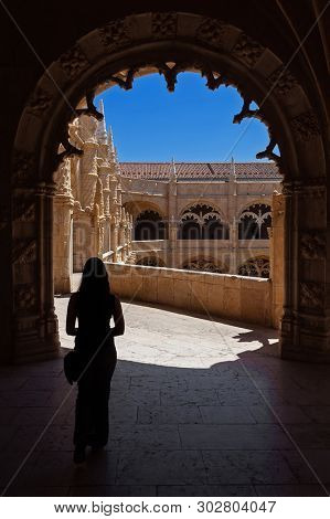 Lisbon, Portugal - June 30, 2018: Young woman visiting the cloister of the Jeronimos Monastery or Abbey aka Santa Maria de Belem monastery. UNESCO World Heritage.