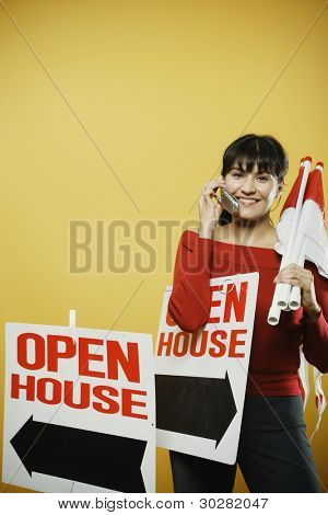 Female realtor carrying signs