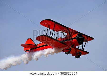 Red Retro Airplane (biplane) Isolated On Blue Sky Background. Vintage Old Red Airplane & Pilot Flyin