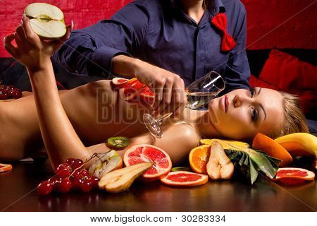 Man giving glass of champagne to naked woman decorated  by fruits