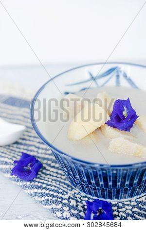 Banana In Coconut Milk On Wooden Table. Thai Dessert