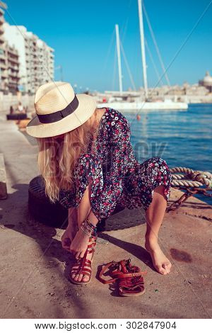 Mediterranean Fashionable Woman Put On Shoes At Sea Dock