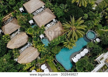 Aerial View Of Luxury Hotel With Straw Roof Villas And Pools In Tropical Jungle And Palm Trees. Luxu