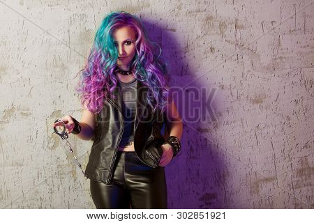Daring Rebel Rocker, A Portrait On A Background Of Gray Grunge Wall. Young Stylish Woman In Black Le