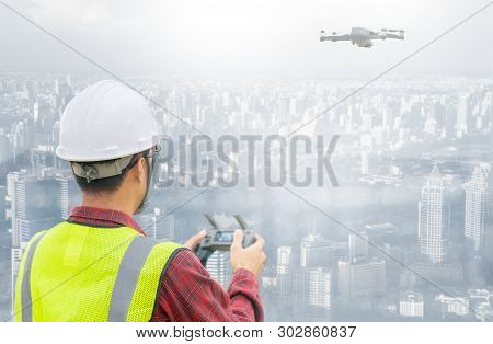 Drone Operated By Construction Worker On Building Site. Construction Worker Piloting Drone At Buildi