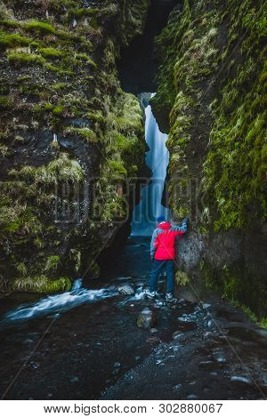 Hiker In Red Coat Peaking Inside A Cave That Contains A Waterfall.