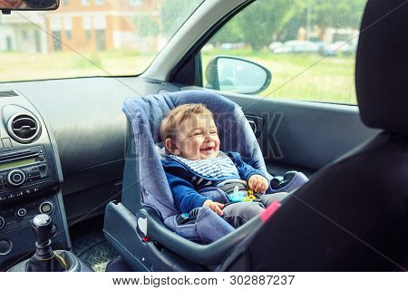 Happy Baby Boy Sitting In A Car In Safety Chair. Protection In The Car.
