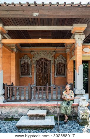Dusun Ambengan, Bali, Indonesia - February 25, 2019: Family Compound. Older Lady Sits In Front Of On