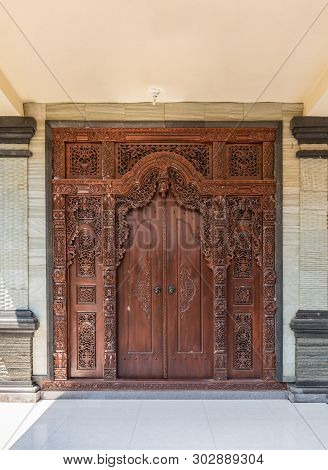 Dusun Ambengan, Bali, Indonesia - February 25, 2019: Family Compound. Brown Decorated Entrance Door