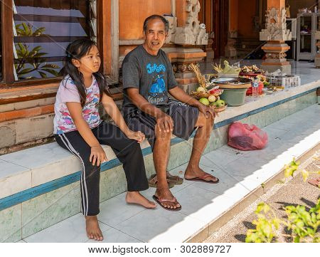 Dusun Ambengan, Bali, Indonesia - February 25, 2019: Family Compound. Father And Young Daughter Sit