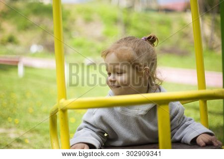 little beautiful red-haired girl hung on a swing, baby plays on a swing on the playground on a warm summer day poster