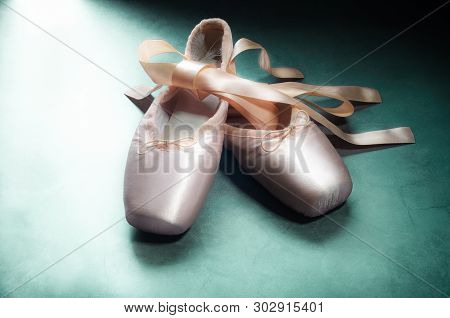 Pointe Shoes Ballet Dance Shoes With A Bow Of Ribbons Beautifully Folded On A Green Background.