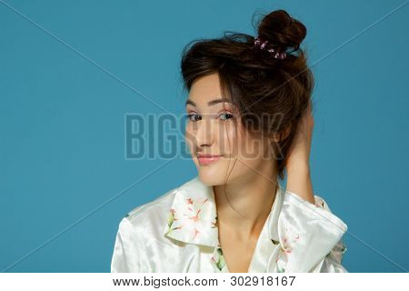 Cheerful attractive sleepy teen girl wearing pyjamas looking at camera like at mirror in the morning, isolated over blue background. Young pretty woman in early before morning procedures.