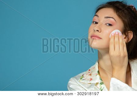 Cheerful attractive teen girl clean her face with cotton disk, isolated over blue background. Portrait of young beautiful woman during morning procedures