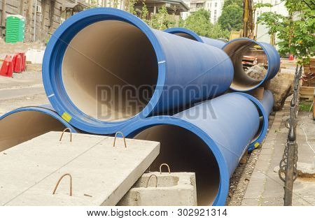 Corrugated water pipes of blue color, large diameter, prepared for laying plumbing or sewerage. poster