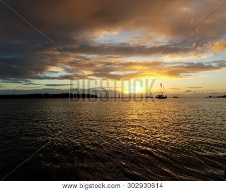 A Vibrant Nautical Golden-yellow Coloured Nimbostratus Cloudy Sunrise Seascape Over Sea Water With W