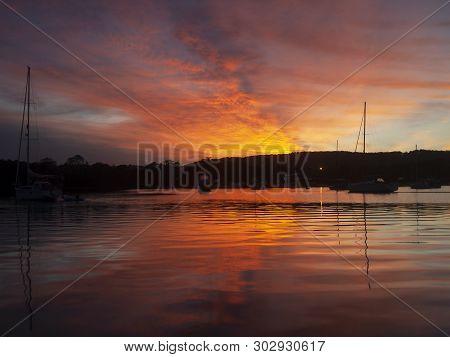 A Brilliant Inspirational Red-orange Coloured Stratocumulus Cloudy Sunrise Seascape Over Calm Sea Wa