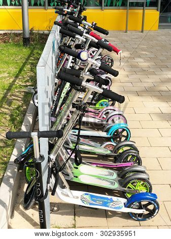 Hannover, Germany - May 24, 2019: Row Of Childrens Scooters Parked Outside School Building.