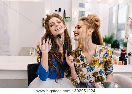 Two amazing joyful models having fun together in  haidresser salon. Preparing to party, expressing true positive emotions, laughing, smiling, coiffure, makeup, professional beauty. poster
