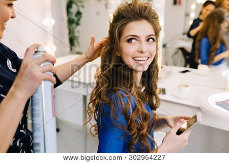 Preparation to celebrating in beauty salon of happy attractive model smiling to stylist. Beautiful coiffure, long curly brunette hair, cheerful mood, making hairstyle. poster