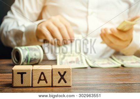 Wooden Blocks With The Word Tax And A Businessman Who Counts Money. The Concept Of Time Payment Of T