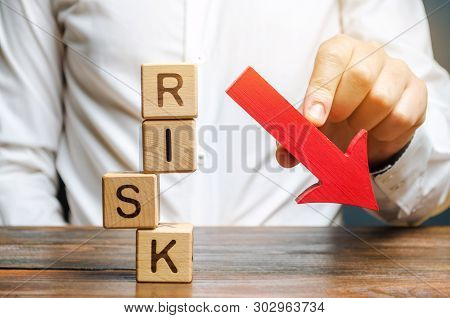 Wooden Blocks With The Word Risk And A Down Arrow. Reduce Financial Risk For Investment And Capital.