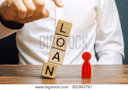 Wooden Blocks With The Word Loan Fall On A Miniature Person. The Concept Of Large Lending Rates For