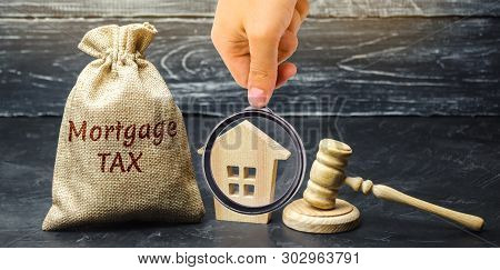 Money Bag With The Word Mortgage Tax, Judge's Hammer And Wooden House. Mortgage Credit Lending. Tax
