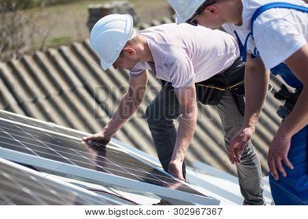 Male Engineers Installing Stand-alone Solar Photovoltaic Panel System. Two Electricians Mounting Blu