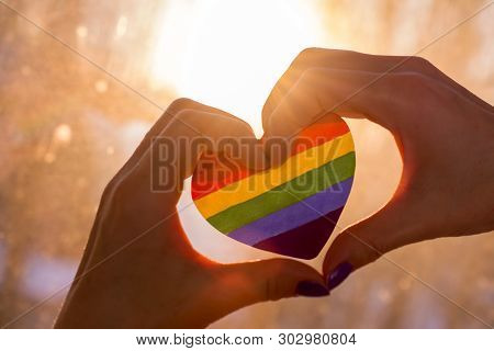 Lgbt Discrimination, Chained Hand Hold Heart Lgbt Flag. Close Up, Selective Focus , Blurred Dark Bac