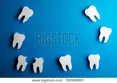 White Healthy Teeth Over Blue Background  With Copy Space. Dental Care And Whitening Teeth. Tooth Re