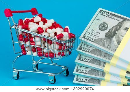 Shopping Cart Filled Red Medicinal Capsules, Wad Of Dollar Money, Blue Background. Most Expensive Dr