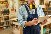 Mid section portrait of senior carpenter using tablet while working in joinery, copy space poster