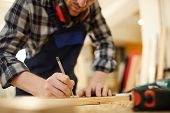Mid section portrait of modern carpenter marking wood while working in joinery lit by sunlight, copy space poster