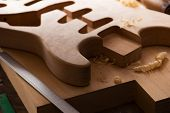 Electric guitar making. Guitar work shop. Unfinished solidbody electric guitar body on work bench. Shallow depth of field.   poster