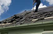 Removing old shingles to prepare a roof for a new installation with blue sky poster