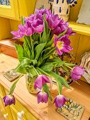 Vase of brightly coloured flowers on a yellow cottage Welsh dresser. Beautiful pink and yellow tulips close up. poster