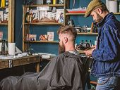Barbershop concept. Barber with hairdryer blows off hair out of cape. Hipster bearded client got hairstyle. Barber with hairdryer works on hairstyle for bearded man, barbershop background poster