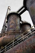 Smokestacks, tubes, and pipes with heavy rust patina, catwalks, vertical aspect poster