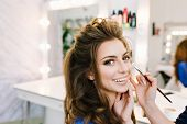 Stylish closeup portrait of gorgeous young woman with beautiful coiffure smiling in hairdresser salon. Making makeup, stylist, professional, cheerful mood, world of beauty, hairdressing service. poster