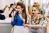 Attractive young women in hurry during preparation to party in hairdresser salon. Making hairstyle, coiffure, makeup, service, being late, astonished, expressing true emotions. poster