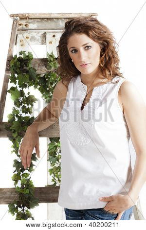 Beautiful woman standing by an old ladder