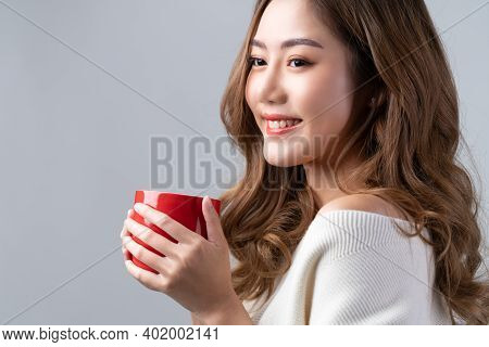Asian Beautiful Girl Holding Red Coffee Cup And Smiling With Calm And Relaxing Expression. Optimisti