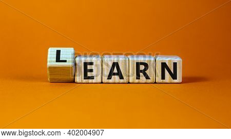 Learn Or Earn Symbol. Turned A Cube And Changed The Word 'earn' To 'learn'. Beautiful Orange Backgro
